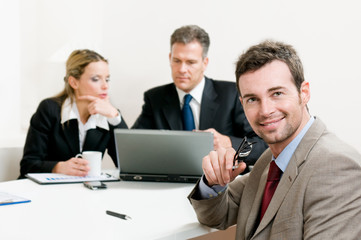 Smiling satisfied businessman at meeting