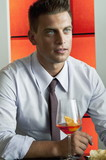 Young man in business suit sitting with glass of orange wine
