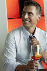 Young man in business attire with glass of orange wine adjusting tie