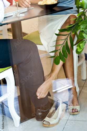 Young woman's bare foot touching young man's leg under table