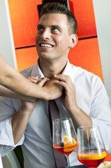 Young woman's arms adjusting young man's tie
