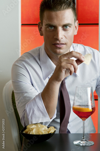 Young man sitting with a glass of orange wine and potato chips