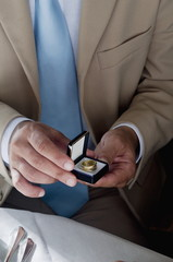 Closeup of hands of young man holding a ring in an open jewelry box