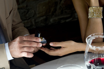 Closeup of hands of young man giving a ring to young woman