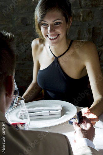 Young woman smiling at young man giving her a ring