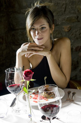 Young woman with plate of food and wine at restaurant