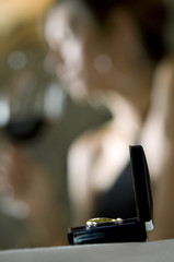 Closeup of ring with young woman in the background drinking red wine