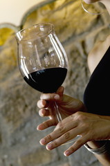 Closeup of red wine in a glass held by young woman's hands