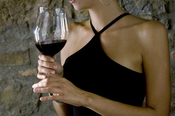 Closeup of red wine in a glass held by young woman