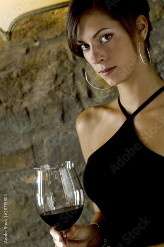 Young woman with a glass of red wine at restaurant