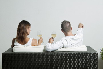 View of couple from the back sitting on couch drinking white wine, young man pointing