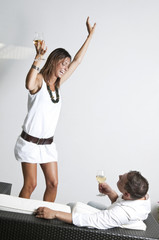 Young woman with white wine dancing next to couch with young man and wine