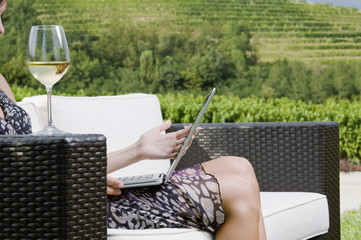 Young woman sitting on couch in vineyard with white wine and laptop