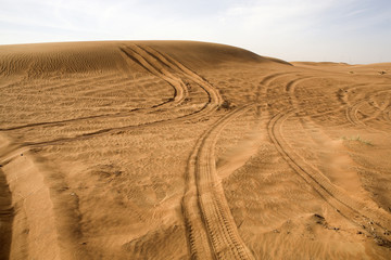 Landscape of Dubai desert with tracks of cars in UAE.