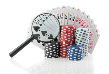 gambling chips and cards with a magnifying glass for casino game