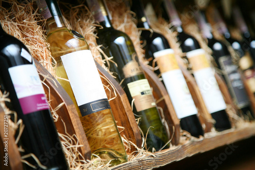 Closeup shot of wineshelf. Bottles lay over straw. - 20727251