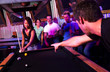 Young adults at a nightclub playing pool