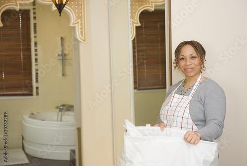 femme de chambre dans un h tel ramasser des serviettes photo libre de droits sur la banque d. Black Bedroom Furniture Sets. Home Design Ideas
