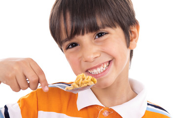 Smiling young boy with spoon of flakes, closeup