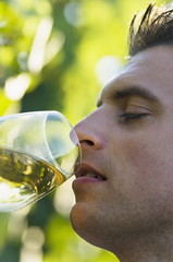 Young man tasting white wine in vineyard