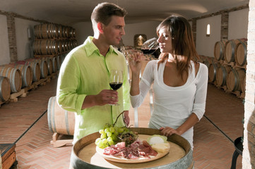 Couple in a wine cellar tasting red wine and antipasti