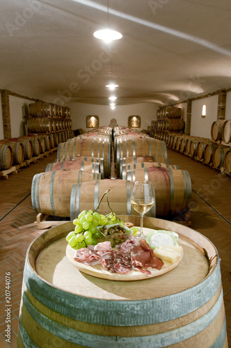 Antipasti platter and glass of white wine with barrels of wine in a cellar