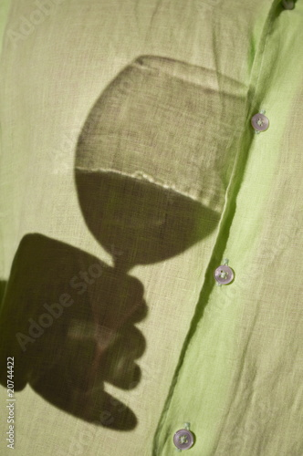 Young man's torso with shadow of hand holding wine glass