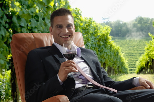 Young man in business suit sitting with glass of red wine