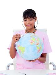 Portrait of a female doctor examining a terrestrial globe