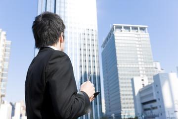 手帳を持ってビルを見上げるビジネスマン
