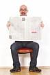 Mann sitzt auf Stuhl und liest Zeitung