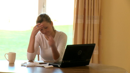 Annoyed woman doing her accounts at home