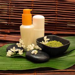 SPA cosmetics series. Cosmetics bottles, mud, stone and white fl