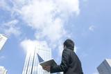 ノートパソコンを片手に空を見上げるビジネスマン