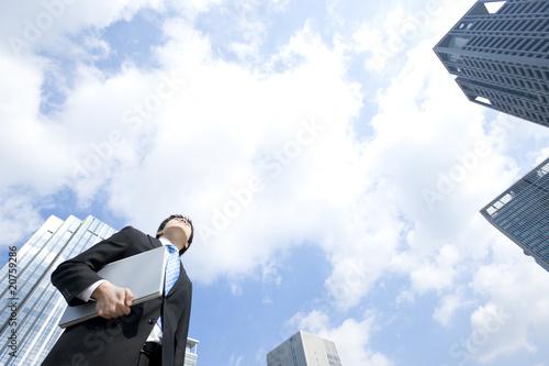 ノートパソコンを抱え空を見上げるビジネスマン