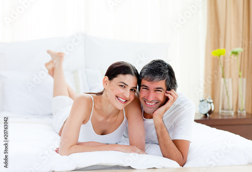 Romantic couple embracing lying on their bed