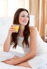 Beautiful woman drinking orange juice on bed