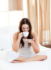 Pretty woman drinking coffee sitting on bed