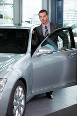 Portrait of car salesperson getting in car at showroom