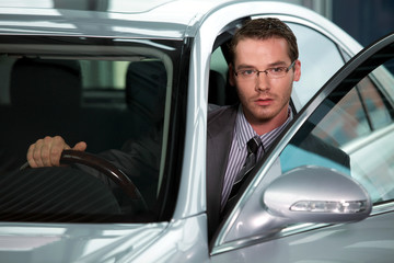 Car salesperson getting in car at showroom