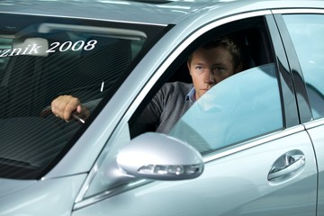 Young man contemplating in new car