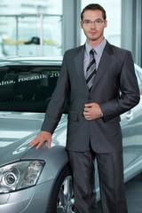 Portrait of car salesperson standing in car showroom