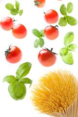 tomatoes and basil falling on spaghetti