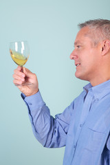 Man holding a glass of white wine checking it's clarity