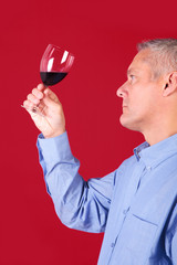 Man checking a glass of red wine for clarity