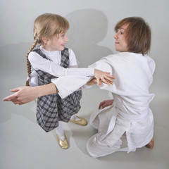 young man in  kimono  fighting with little girl