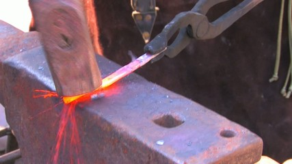 HD Glowing iron ready for blacksmith with hammer, closeup
