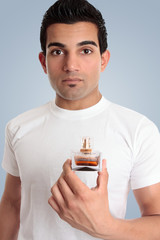 A man holds a bottle of cologne
