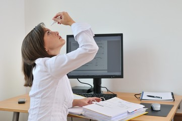 Young business person applying eyes drops