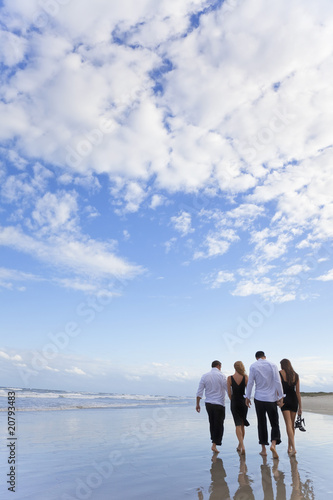 Four Young People, Two Couples, Walking On A Beach